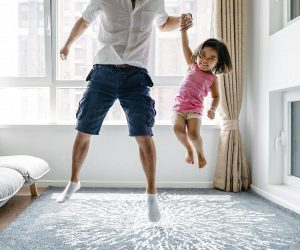 a man jumps holding his young smiling daughter by the hand