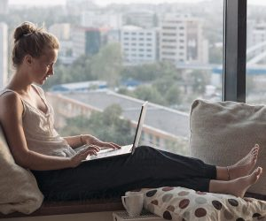 woman lounges while working on laptop near large window