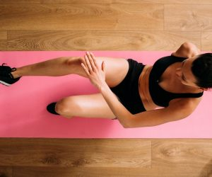woman on pink exercise mat exercises