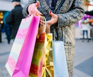 woman in peacoat carries brightly colored shopping bags