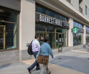 two men with bags walk in front of Barnes and Noble