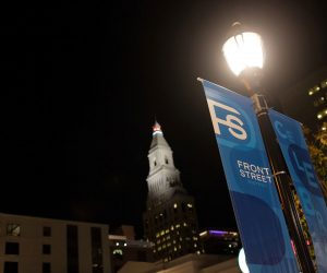 """streetlamp lit at night with banners labeled '""""Front Street"""" hanging"""