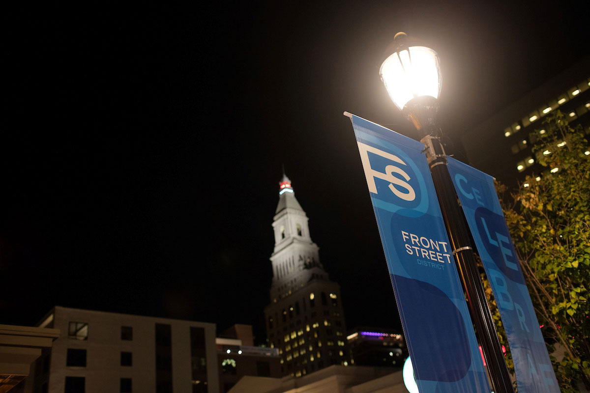 "streetlamp lit at night with banners labeled '""Front Street"" hanging"