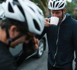 man in a biking helmet sips coffee with a friend