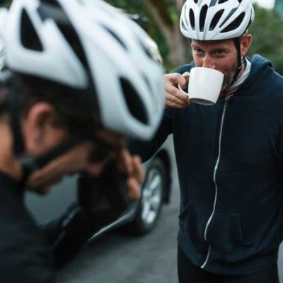 man in a biking helmet sips coffee with a friend
