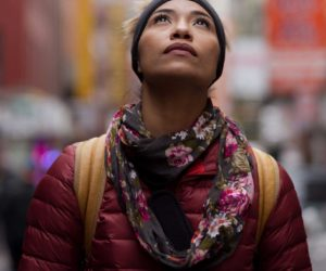 woman with floral scarf looks upwards